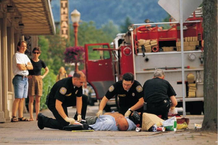 Picture of an emergency first responder giving a man CPR on a sidewalk